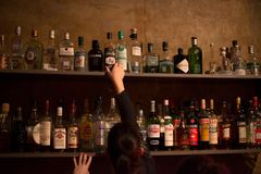 Waitress and bar shelves full of alcoholic beverages bottles Royalty Free Stock Images