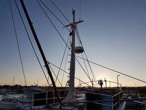 Stuurwiel op de brug van een vissersboot in een jachthaven wordt vastgelegd die Panorama van de avondzonsondergang in de haven va stock afbeelding