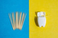 Stuzzicadenti su fondo blu e su filo per i denti in contenitore bianco sul contesto giallo, vista superiore fotografie stock libere da diritti