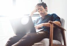 stwarzać ognisko domowe pracujących mężczyzna potomstwa Obsługuje używać współczesnego laptop i hełmofony w rocznika krześle podc Obrazy Royalty Free