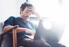 stwarzać ognisko domowe pracujących mężczyzna potomstwa Obsługuje używać współczesnego laptop i hełmofony w rocznika krześle podc Obraz Stock
