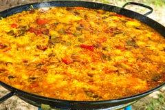 Stwarza ognisko domowe gotującego Hiszpańskiego Valencian paella w wielkiej płaskiej smaży niecce Rozmaitość mięsa, warzywa, ryż, Obraz Royalty Free
