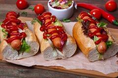 Stwarza ognisko domowe robić hot dog - ściska z sałatą na drewnianym tle Obrazy Royalty Free