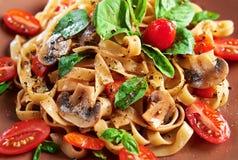 Stwarza ognisko domowe robić weganinu makaron z pieczarkami, pomidorami, basilem, pieprzami i aubergines słuzyć na talerzu przy d Obraz Royalty Free