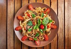 Stwarza ognisko domowe robić weganinu makaron z pieczarkami, pomidorami i basilem, Obraz Royalty Free