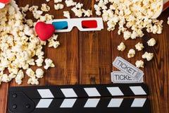 Styckar i lotter popcorn, 3D-glasses, hjärta, filmbiljetter och filmclapperen Fotografering för Bildbyråer