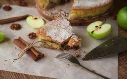 Stycke av äppelpajen med kanel och valnötter på en trätabell Royaltyfri Foto
