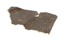 Stycke av använd sandpapper på en vit bakgrund Arkivbild