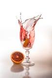 Stycke av apelsinen som faller i ett exponeringsglas arkivfoton