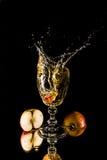 Stycke av appel som faller i ett exponeringsglas Royaltyfri Fotografi