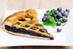 Stycke av blåbärpajen på maträtt Arkivfoto