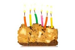 Stycke av caken med burning stearinljus Royaltyfria Foton