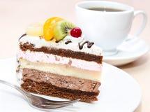 Stycke av chokladkakan med frukt Arkivfoto