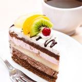 Stycke av chokladkakan med frukt på plattan Royaltyfri Foto
