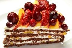 Stycke av chokladkakan med kräm och frukt Royaltyfri Fotografi