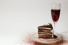 Stycke av chokladkakan på ett glass tefatexponeringsglas av rött vin Royaltyfri Bild