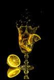 Stycke av citronen som faller i ett exponeringsglas royaltyfri fotografi