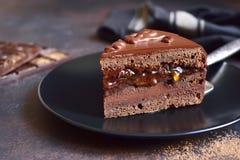 Stycke av den chokladSacher torten på en svart platta på en kritisera, ston arkivbilder