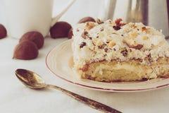 Stycke av den kräm- kakan på den vita plattan Royaltyfri Foto