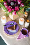 Stycke av den läckra kakan för chokladmousse på den färgrika plattan på trätabellbakgrund Tabellinställning med blommor och stear Arkivbild
