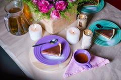 Stycke av den läckra kakan för chokladmousse på den färgrika plattan på trätabellbakgrund Tabellinställning med blommor och stear Royaltyfria Bilder
