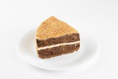 Stycke av den ljusbruna kakan i en plattaisolat på vit bakgrund arkivfoto
