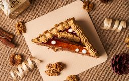 Stycke av den ljusbruna kakan med choklad Fotografering för Bildbyråer