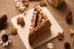 Stycke av den ljusbruna kakan med choklad Arkivbild