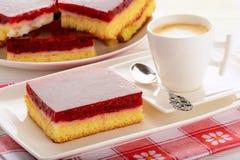 Stycke av den ljusbruna kakan med kräm och körsbärsröd gelé och kopp kaffe Royaltyfria Bilder