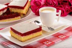 Stycke av den ljusbruna kakan med kräm och körsbärsröd gelé och kopp kaffe arkivbild