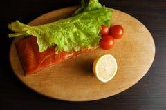 Stycke av den röda fisken med citronen och körsbärsröda tomater på ett träbräde fotografering för bildbyråer