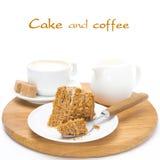 Stycke av honungkakan på en platta, en kräm och en kopp av cappuccino Royaltyfria Bilder