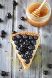 Stycke av honungkakan som dekoreras med blåbäret Royaltyfri Fotografi
