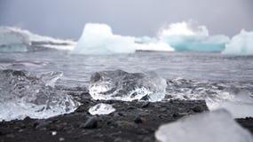 Stycke av is i Island, isberg, svart strandsand Arkivfoto