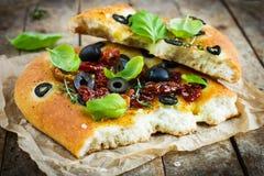 Stycke av italienskt focacciabröd med svarta oliv, torkad tomatoe Royaltyfria Bilder