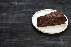 Stycke av kakan på den vita plattan Royaltyfri Bild