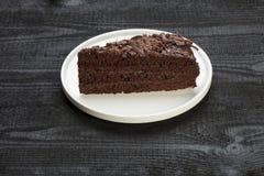 Stycke av kakan på den vita plattan Royaltyfri Foto