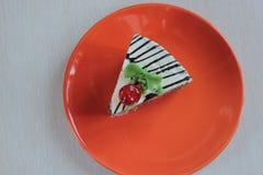 Stycke av kakan på en orange maträtt fotografering för bildbyråer