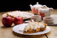 Stycke av kakan som dekoreras med piskad kräm med teaware och appl Fotografering för Bildbyråer