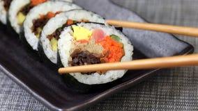 Stycke av koreansk maträttgimbap eller kimbap med tonfisk och grönsaker som tas från plattan med pinnar arkivfilmer