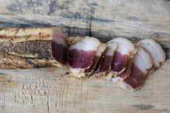 Stycke av kurerat griskött på ett träbräde arkivfoton