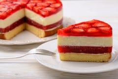 Stycke av läcker ostkaka med jordgubbemousse, jordgubbegelé och jordgubbar Royaltyfria Bilder