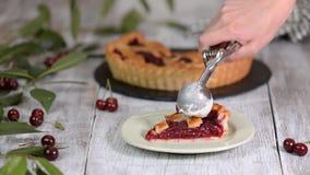 Stycke av läckra hemlagade Cherry Pie med en glass på lantlig trävit bakgrund lager videofilmer