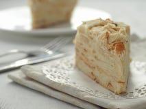 Stycke av mång- i lager kakanärbild Mille feuilleefterrätt Smulor dekorerade torten på den vita doilyen på trätabellen Royaltyfria Bilder