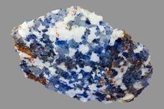 Stycke av mineraliskt för halite som isoleras på grå bakgrund arkivfoto