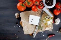 Stycke av mjuk ost på brädet och marinerad kryddig feta i a Arkivfoton