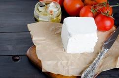 Stycke av mjuk ost på brädet och marinerad kryddig feta i a Arkivbilder