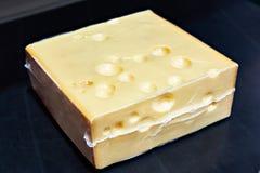 Stycke av ost i vakuumplast- arkivbilder