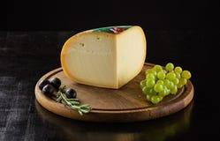 Stycke av ost, svarta oliv och druvor på träbräde royaltyfri foto
