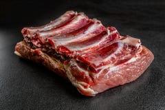 Stycke av rå grisköttstöd på mörk bakgrund Royaltyfri Fotografi